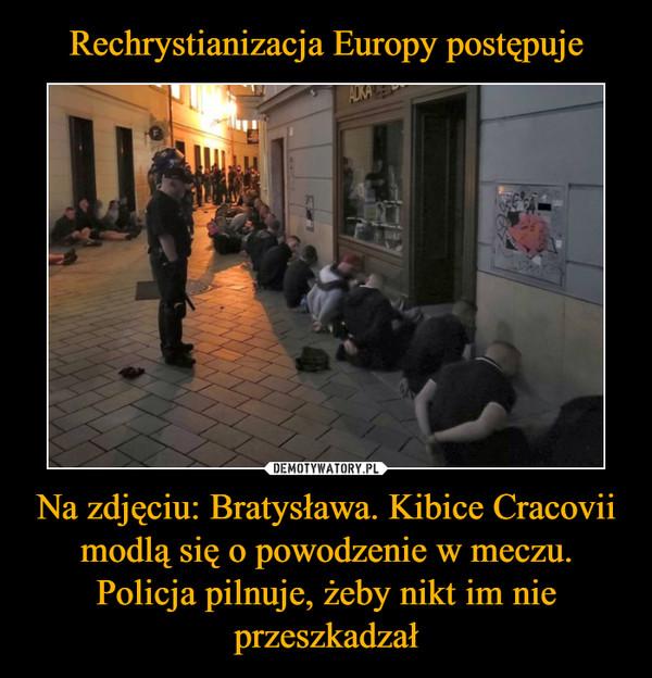 Na zdjęciu: Bratysława. Kibice Cracovii modlą się o powodzenie w meczu. Policja pilnuje, żeby nikt im nie przeszkadzał –