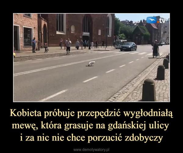 Kobieta próbuje przepędzić wygłodniałą mewę, która grasuje na gdańskiej ulicy i za nic nie chce porzucić zdobyczy –